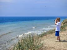 Troszkę chłopiec spojrzenia przez lornetek przy morzem obraz stock