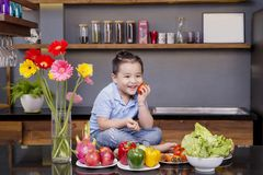 Troszkę chłopiec w kuchni z mnóstwo owoc i warzywo Zdjęcie Royalty Free