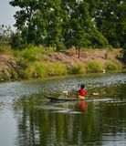 Troszkę chłopiec wiosłuje drewnianą łódź na kanale zdjęcie stock