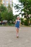 Troszkę dziewczyna bawić się badminton w jardzie mieszkanie buiding Zdjęcie Stock