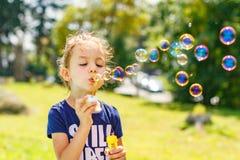Troszkę dziewczyna dmucha mydlanych bąble w lato parku fotografia stock