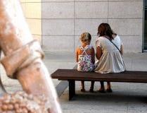 Troszkę dziewczyna i jej matka sitted na ulicznej ławce fotografia stock
