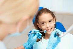 Troszkę dziewczyna przy przyjęciem z dentysta kobiety lekarki narządzaniem egzamininować zęby dziewczyna dziewczyna odizolowywają Zdjęcia Stock