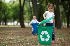 Troszkę dziewczyna stawia wiadro dekiel na zielonym przetwarza koszu na zamazanym naturalnym tle Ekologia i dzieci zdjęcia stock