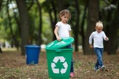 Troszkę dziewczyna stawia wiadro dekiel na zielonym przetwarza koszu na zamazanym naturalnym tle Ekologia i dzieci obraz stock