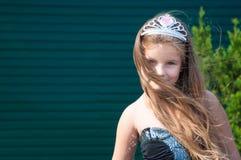 Troszkę dziewczyna w czarnej sukni z koroną, długie włosy, na zielonym tle, dzień, wiatr princess, troszkę Obrazy Stock
