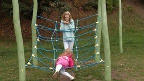 Troszkę dziewczyna w różowej sukni i jej matka bawić się z linową drabiną w boisku zbiory wideo