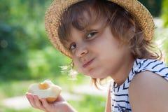 Troszkę dziewczyna z chytrym uśmiechem w słomianym kapeluszu, żuć jabłka, lato wakacje obrazy royalty free