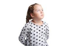 Troszkę dziewczyna z poważnym spojrzeniem, przyglądające up mienie ręki za plecy pojedynczy białe tło zdjęcie stock