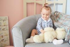 Troszkę dziewczyny bawić się w domu dla lal z niedźwiedziem Zdjęcie Stock