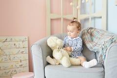 Troszkę dziewczyny bawić się w domu dla lal z niedźwiedziem Obraz Royalty Free