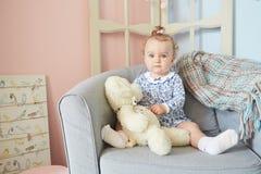 Troszkę dziewczyny bawić się w domu dla lal z niedźwiedziem Zdjęcia Stock