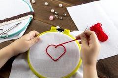Troszkę haftuje serce na widoku białych sukiennych akcesoriach dla broderii na drewnianym tle z góry dziewczyna obraz stock