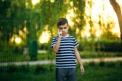 Troszkę jest uśmiechnięta i doping chłopiec w pasiastej koszulce Wiosna, pogodna pogoda Obraz Stock