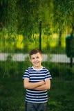 Troszkę jest uśmiechnięta i doping chłopiec w pasiastej koszulce Wiosna, pogodna pogoda zdjęcie stock