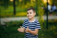 Troszkę jest uśmiechnięta i doping chłopiec w pasiastej koszulce Wiosna, pogodna pogoda Fotografia Stock