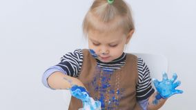 Troszkę odziewa w farbie dziewczyna rysująca ręki i podczas gdy Dziecko ostrożnie egzamininuje brudne ręki zbiory