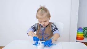 Troszkę odziewa w farbie dziewczyna rysująca ręki i podczas gdy Dziecko ostrożnie egzamininuje brudne ręki zbiory wideo