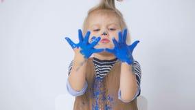 Troszkę odziewa w farbie dziewczyna rysująca ręki i podczas gdy Dziecko ostrożnie egzamininuje brudne ręki zdjęcie wideo