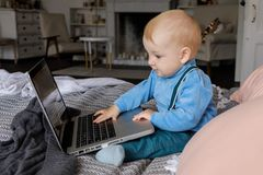 Troszkę patrzeje ciekawie przy laptop książką chłopiec i zdjęcie stock