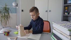Troszkę piękny facet w zmroku - błękit koszula robi pomiarom układ cegła dom który stoi na jego biurku zdjęcie wideo