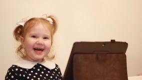 Troszkę raduje się oglądać wideo na internecie i ono uśmiecha się śliczna dziewczyna Śmieszni dzieci spojrzenia na pastylka ekran zdjęcie wideo