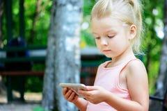 Troszkę siedzi na ławce i spojrzeniach w telefon dziewczyna z blondynem Dziecko fascynuje gadżetem fotografia stock