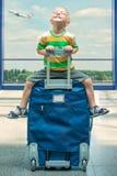 Troszkę siedzi na dużej walizce przy lotniskiem chłopiec czekaj lotu obraz royalty free