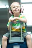 Troszkę siedzi na dużej walizce przy lotniskiem chłopiec czekaj lotu zdjęcia stock