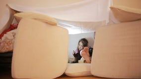 Troszkę siedzi w prowizorycznym domu poduszki i koc dom dziewczyna zdjęcie wideo