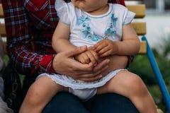 Troszkę siedzi w rękach dziewczyna dziewczyna, ściska za jej i mienie rękami z powrotem zdjęcie royalty free