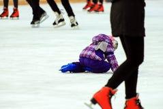 Troszkę spada na lodzie w, jeździć na łyżwach chłopiec i, zima wakacje Szkolni kluby sportowi obraz stock