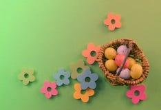 Troszkę stoi na zielonym tle kosz z Easter jajkami fotografia royalty free