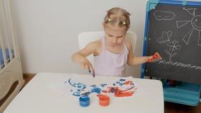 Troszk? rysuje na papierze z jaskrawymi palcowymi farbami ?liczny dziewczyny obsiadanie przy sto?em, maczanie ona palce w s?ojach zdjęcie wideo