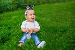 Troszkę siedzi na trawie dziecko w drelichu ubraniach Obraz Royalty Free