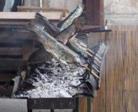 Trote fumate verticalmente e grigliate con gli spiedi di legno sopra la griglia fotografia stock