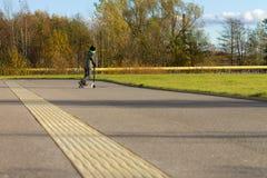 'trotinette' bonito da equitação do menino, exterior no ambiente do outono na luz morna do por do sol foto de stock
