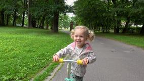 'trotinette' bonito da equitação da menina na estrada do parque vídeos de arquivo