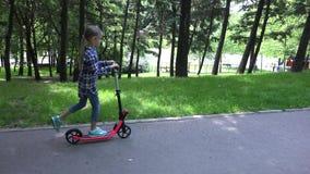 'trotinette' da equitação da criança na menina do parque que relaxa crianças fazendo exteriores do esporte na natureza 4K filme