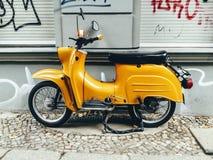 'trotinette' de motor amarelo do vintage estacionado no passeio Imagem de Stock Royalty Free