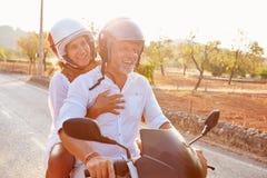 'trotinette' de motor maduro da equitação dos pares ao longo da estrada secundária fotografia de stock royalty free