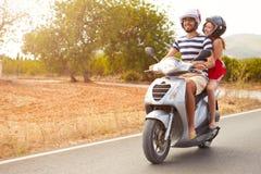 'trotinette' de motor novo da equitação dos pares ao longo da estrada secundária fotografia de stock royalty free