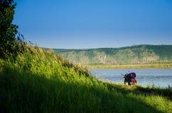 'trotinette' de motor perto de um monte com grama verde perto do rio em um s Fotos de Stock