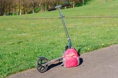 'trotinette' e trouxa ao lado do prado verde Foto de Stock