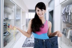 Trotse Aziatische vrouw die haar gewichtsverlies tonen Stock Afbeelding