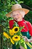 Trotse bejaarde tuinman die haar bloemen bewonderen royalty-vrije stock afbeeldingen