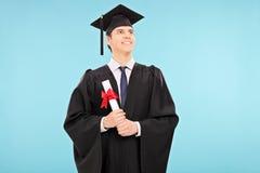 Trotse mannelijke gediplomeerde student die een diploma houden royalty-vrije stock fotografie