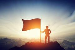 Trotse mens die een vlag op de piek van de berg opheffen Uitdaging, voltooiing royalty-vrije stock foto's
