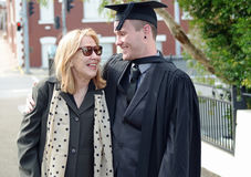 Trotse & moeder en Universitaire Gediplomeerde zoon die glimlachen koesteren royalty-vrije stock fotografie