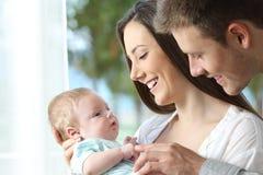 Trotse ouders die met hun baby spelen stock foto's